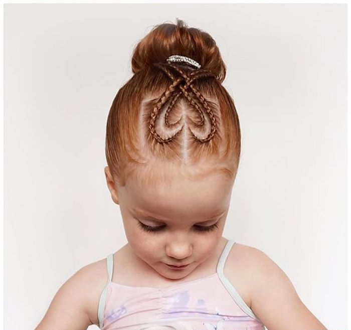 double heart-shapes, formed by two sets of thin braids, on top of a little, ginger girl's head, cute girls hairstyles, bun at the back