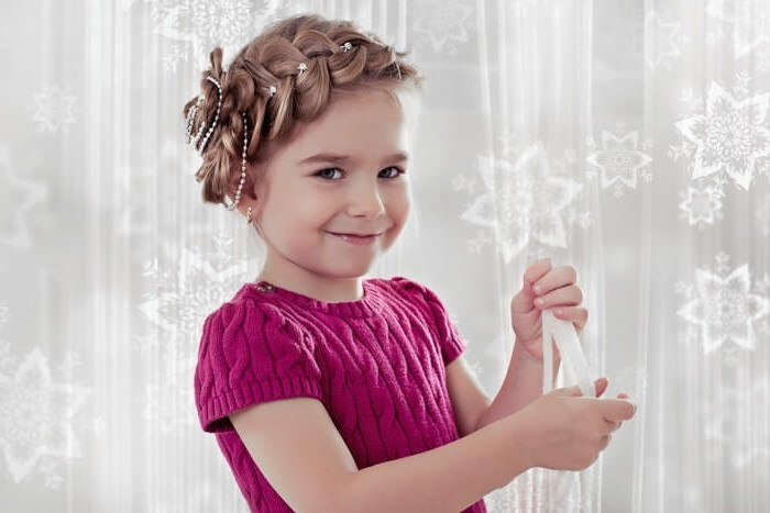 knitted pink sweater, with short sleeves, worn by a smiling young child, with light brunette hair, styled into a crown braid, around her head