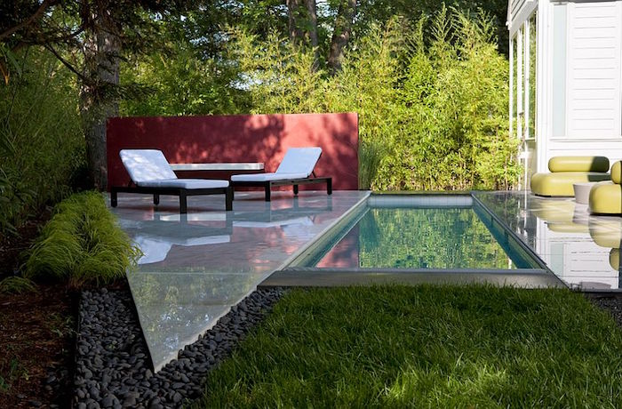 sun beds in white, and a matching table, on a smooth triangular panel, placed in a garden, near a rectangular pool, small backyard pool ideas, grass and pebbles