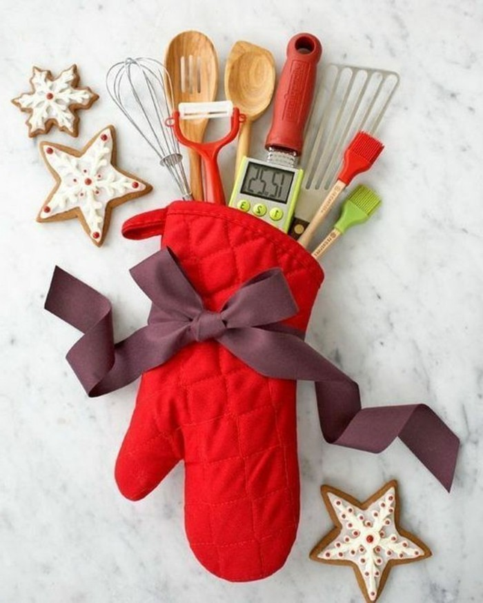 thermometer and wooden spoons, a whisk and a peeler, a spatula and other kitchen utensils, inside a red glove, tied with a purple bow, creative gift ideas, three glazed cookies nearby
