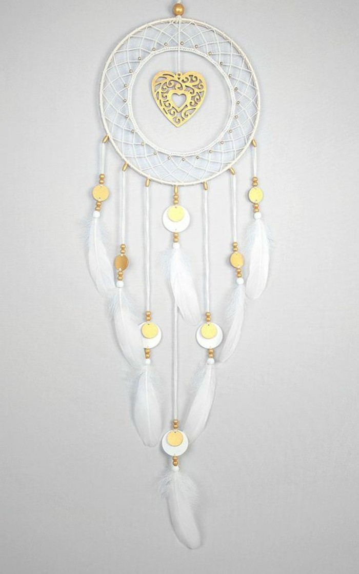 heart ornament in gold, in the middle of a white dream catcher, with white feathers, and more small gold ornaments
