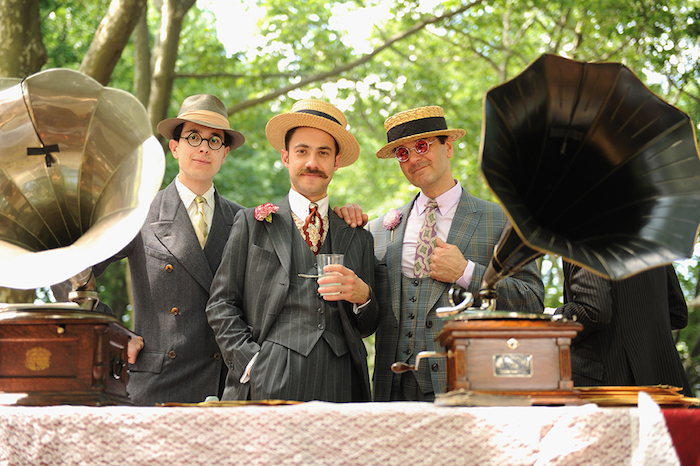 three men in great gatsby outfits, grey three-piece patterned tweed suits, colorful ties and straw hats, two antique gramophones nearby