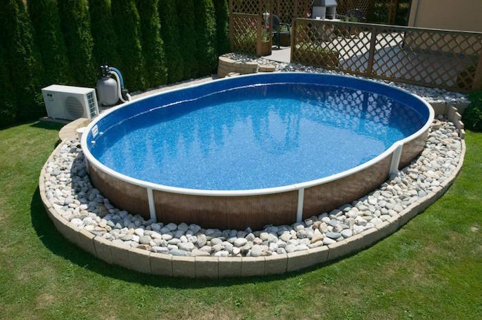 oval pool filled with water, resting on a bed of white stones, in a yard with green grass, small above ground pools, wooden fence nearby
