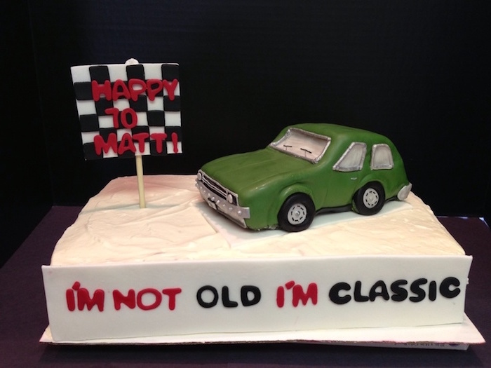 i'm not old i'm classic, written in red and black icing, on the side of a white rectangular cake, topped with a green vintage car, 60th birthday party ideas for men