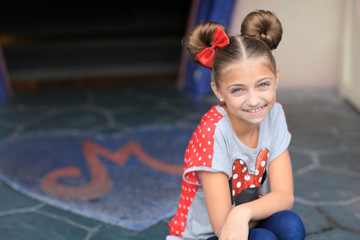 little girl haircuts, symmetrical hair buns, on the head of a smiling, brunette young girl, wearing a minnie mouse t-shirt, and a single red bow
