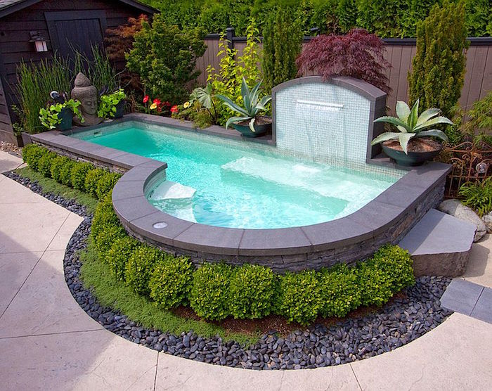 fountain pouring water into a small pool, lined with grey tiles, and decorated with small green shrubs, and various other plants