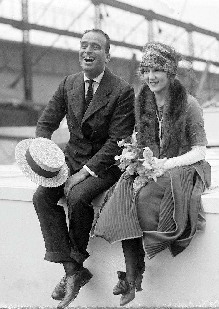roaring 20s dress, on a smiling woman, with a fur shawl and a hat, sitting next to a laughing man, in a vintage suit, authentic antique photo