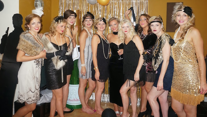 ten women in formal dresses, inspired by the 1920s, and accessorized with faux fur shawls, long pearl necklaces, headbands and other items
