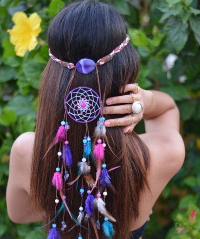 brunette woman with long hair, wearing a small, purple dream catcher, decorated with tiny pink, white and turquoise feathers, in her hair, pictures of dream catchers, leafy green plants, with yellow blossoms in the background