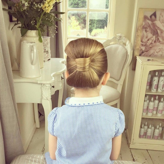 checkered blue and white dress, with a white embroidered collar, worn by a child, with honey blonde hair, braided into a large side bow, girl haircuts, seen from the back