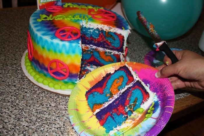 psychedelic birthday cake, multicolored and decorated with neon pink peace signs, 60th birthday color, hand holding a tie-dye patterned paper plate, with one cut slice