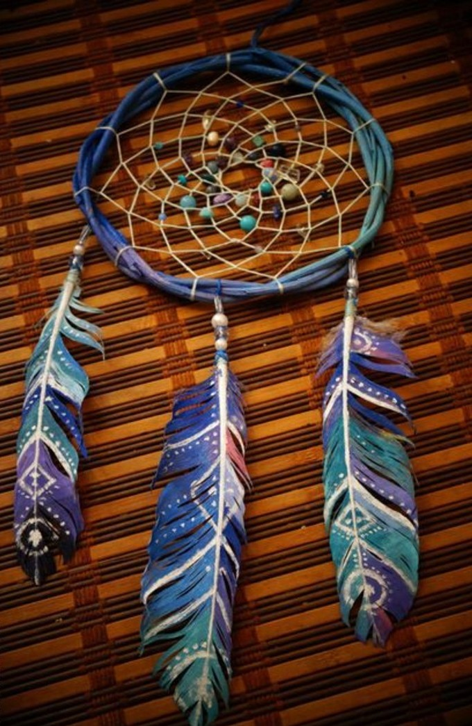 painted feathers in blue, purple and pink, with white hand-drawn symbols, attached to a handmade dreamcatcher