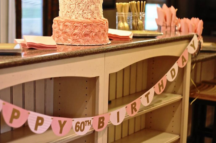 garlands in two shades of pink, decorated with the inscription happy 60th birthday, hung on a wooden counter, with a pink birthday cake, gold cutlery and pink napkins