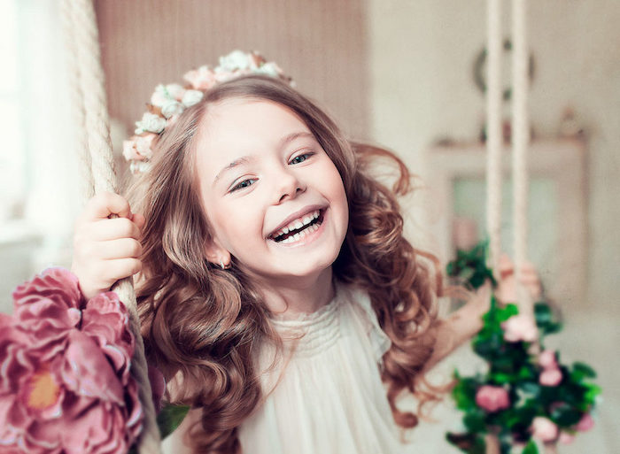 hairstyles for little girls, laughing child with long, curled brunette hair, wearing a flower crown