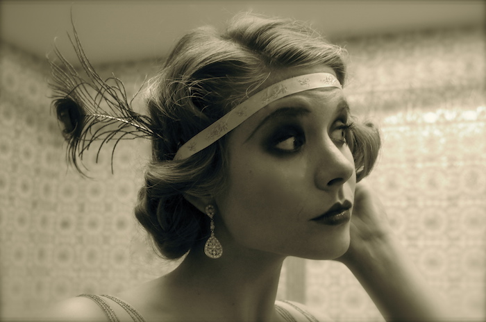 faux vintage photo, with a sepia tint, showing a close up of a woman's head, hair and make up styled like a 1920s flapper