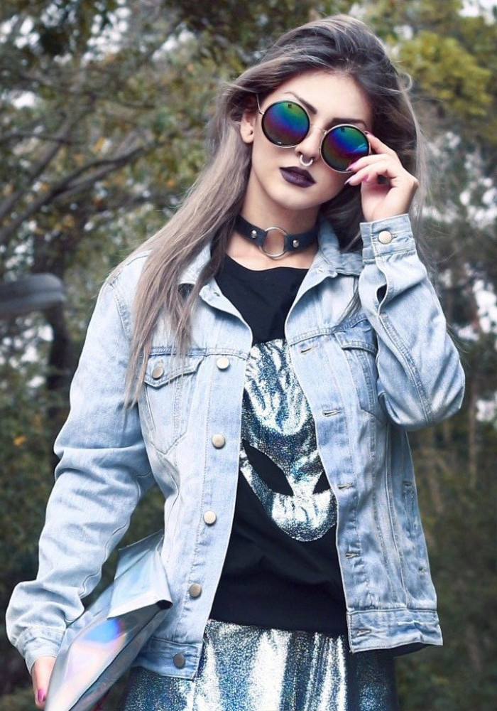 round sunglasses and a nose ring, on a young woman, with a black t-shirt, featuring a holographic alien print, 90s halloween costumes, holographic skirt and a pale denim jacket