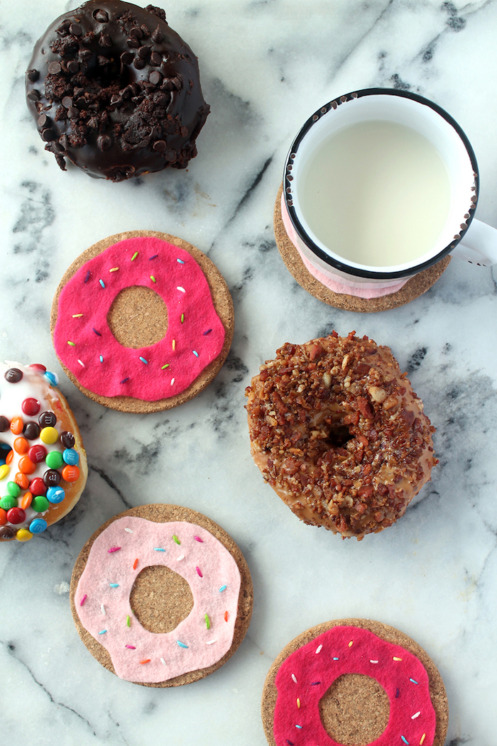 donut shaped coasters made with felt and cork, creative gift ideas, donuts scattered next to white mug, marble countertop