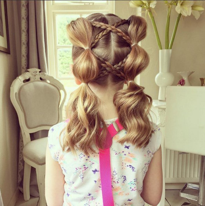 criss-crossing braids, on a child's honey blonde, shoulder-length hair, with pigtails tied in several spots, girl haircuts