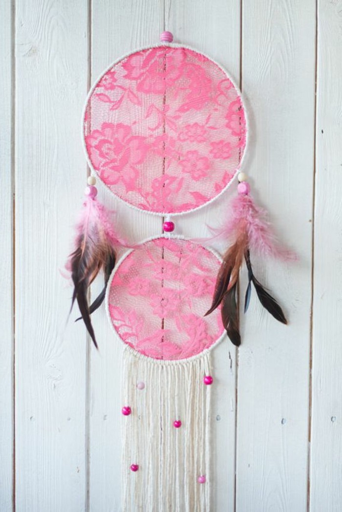 neon pink lace, decorating a white dream catcher, with brown feathers, and white tassels, dreamcatcher designs, white wooden planks in the background