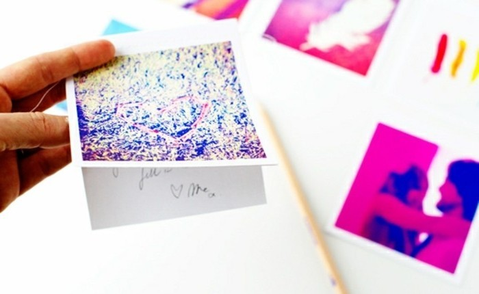 hand holding a diy card, made from a printed photo, decorated with paint, last minute birthday gifts, more printed photos in the background