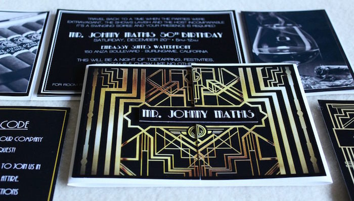 art deco invitation, in black and gold, for a roaring 20s themed party, placed on a white surface, near black and white images and leaflets