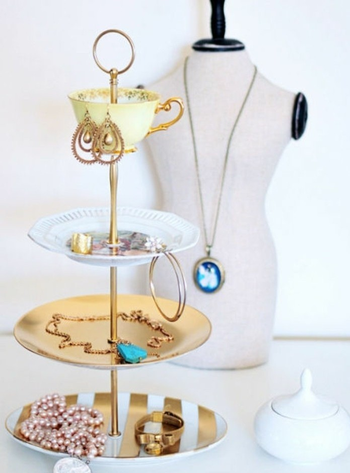 plates and a teacup, spray painted in gold, white and yellow, and attached to a gold pole, to form a jewelry organizer, cute birthday ideas, bracelets and rings, necklaces and earrings inside