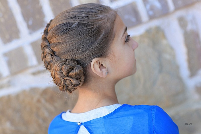blue layered top, worn by a young brunette girl, with a braid, ending in a swirl-like detail, kids hairstyles, seen from the side