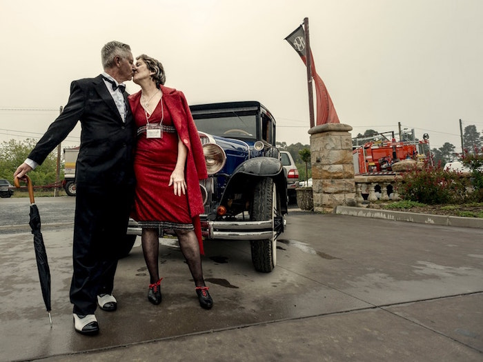 elderly couple dressed in 1920s inspired clothes, kissing in front of a black antique car, red dress and black smocking
