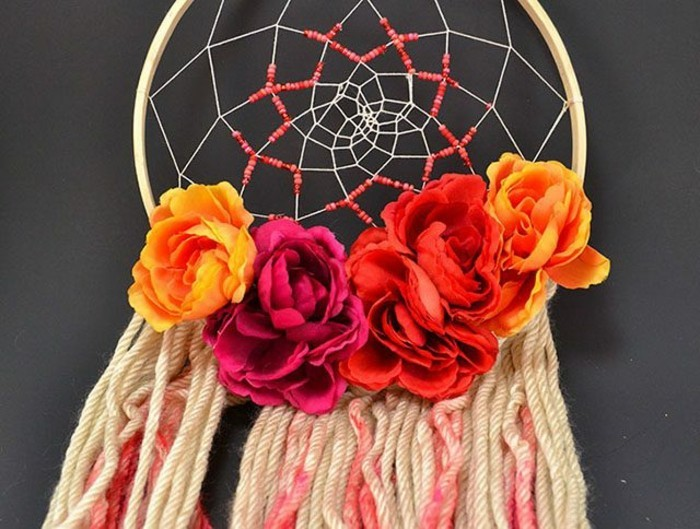 five faux roses, in yellow and orange, and deep red, decorating a dream catcher, with beige and pink tassels, dreamcatcher designs, seen in close up