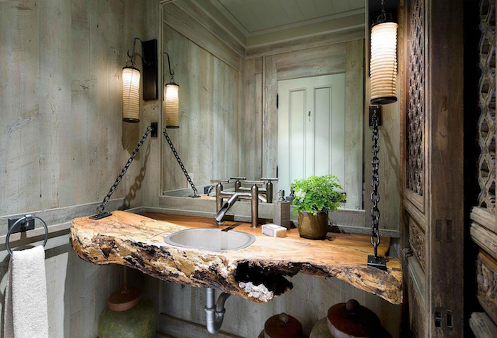 counter made from a large piece of untreated wood, with and inbuilt sink, suspended from a wall, using black chains, a large wall mirror, and wood panelling on the walls, modern bathroom ideas, two lantern lamps, and an ornamental wooden door