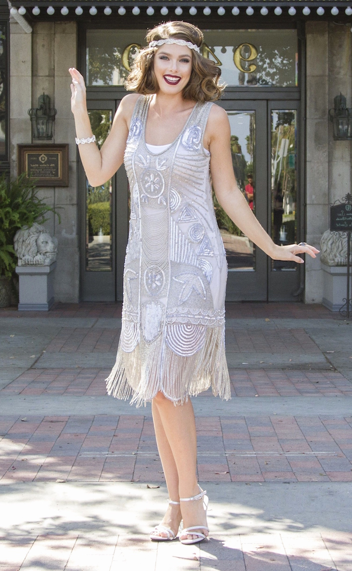 gatsby dress in off-white, featuring art deco-style, silver colored embroidery, with beads and a fringed hem, on a laughing brunette woman