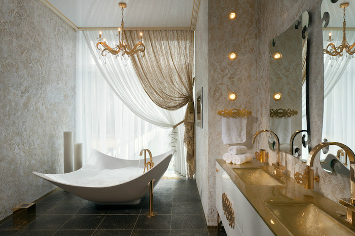gold-colored sinks, in a room with a black tiled floor, containing an unusual square bathtub, nice bathrooms, white and gold curtains