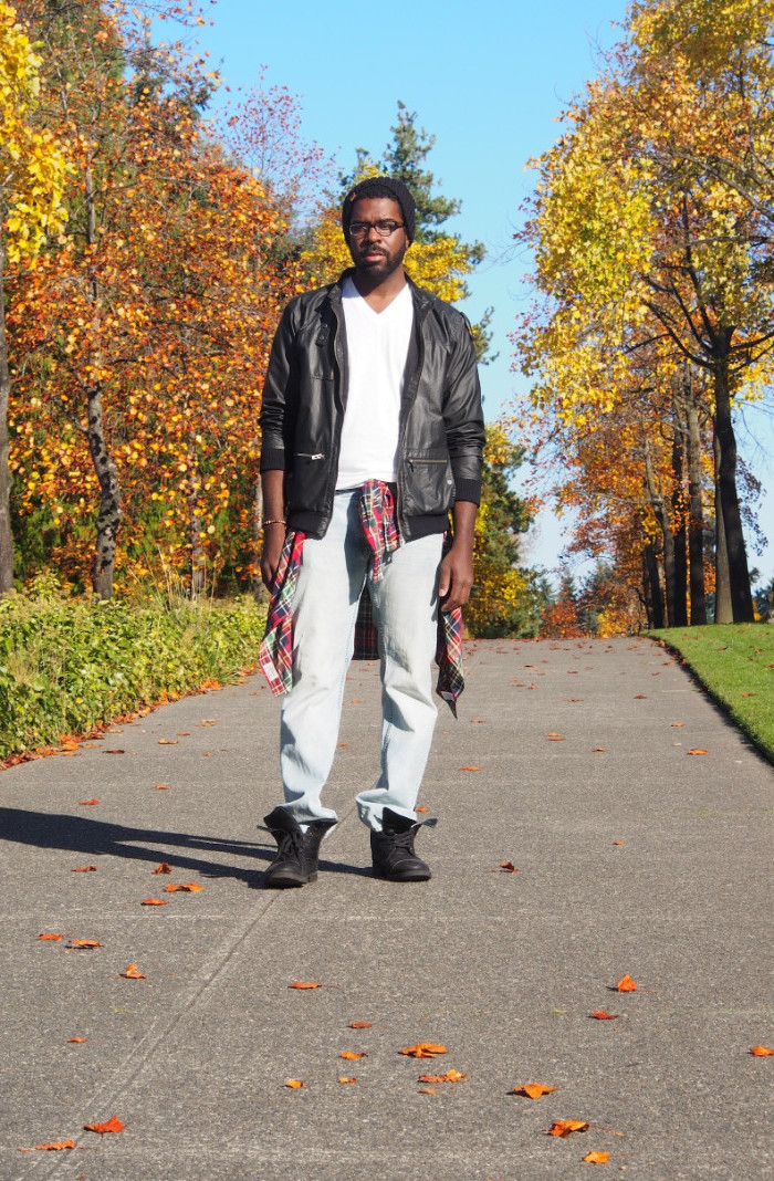 pilot's leather jacket in black, worn over a white v-neck sweater, and pale jeans, 90s aesthetic, worn by a black man, with a flannel shirt tied round the waist