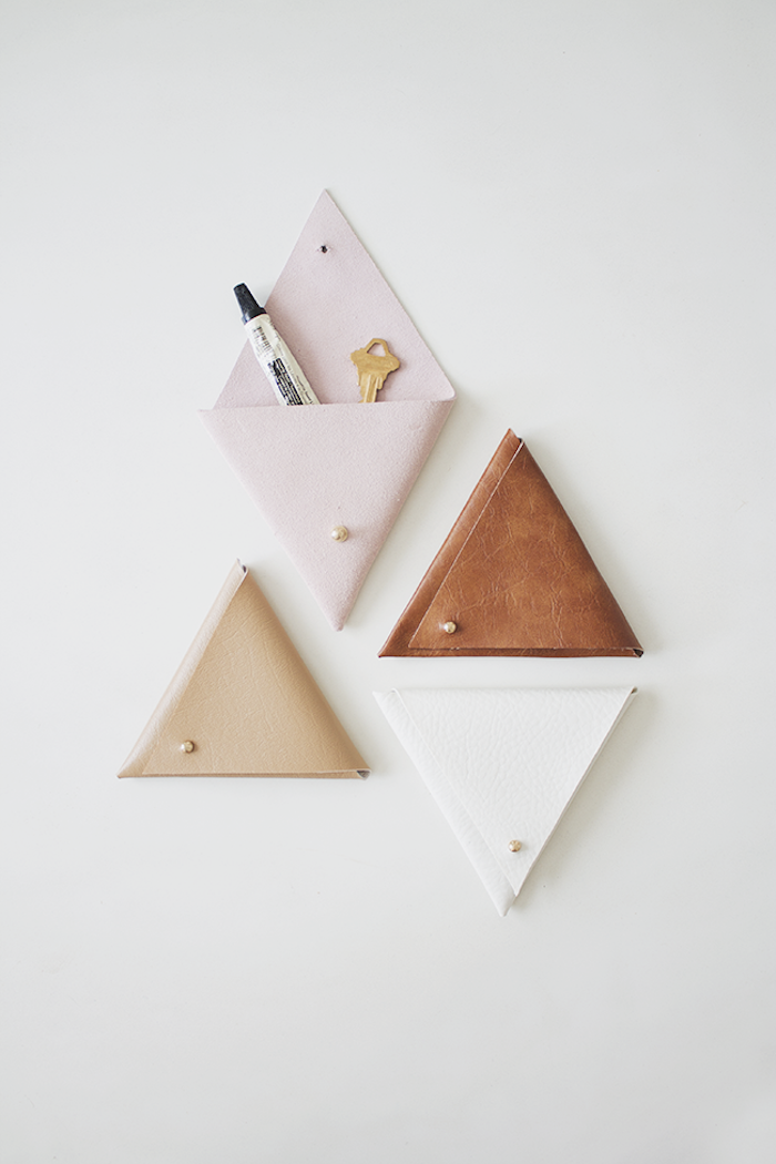 pink beige brown and white leather pouches, mounted on white wall, diy gifts for friends, wall organizers