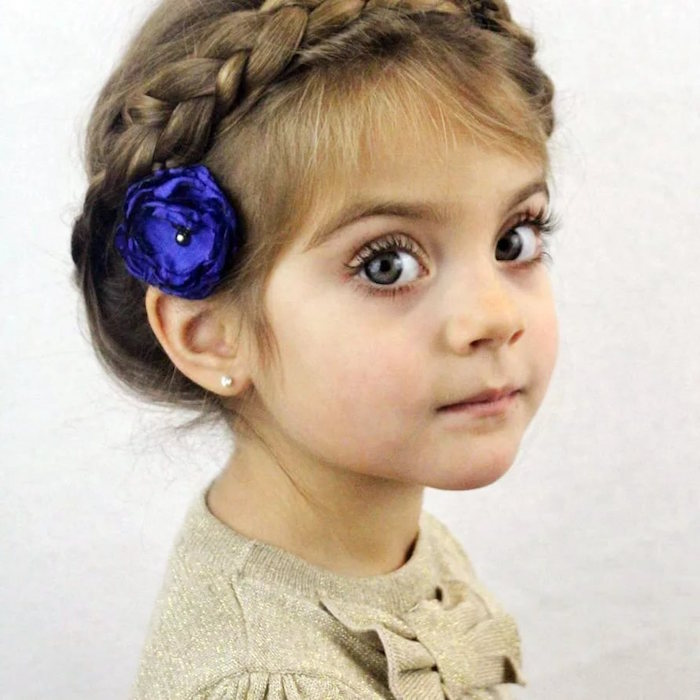 electric violet flower ornament, behind the ear of a small child, with big blue eyes, and light brunette hair, woven into a crown braid