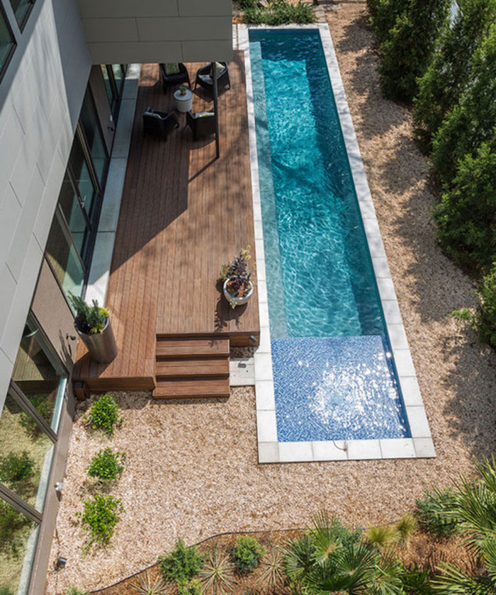 narrow and long pool, in a yard covered with beige pebbles, green shrubs and other plants, house with a patio