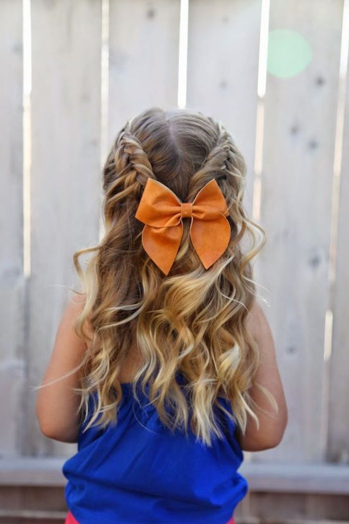 orange hair bow, decorating two joining braids, on the back of a girl's head, long curled dark blonde hair, with natural highlights