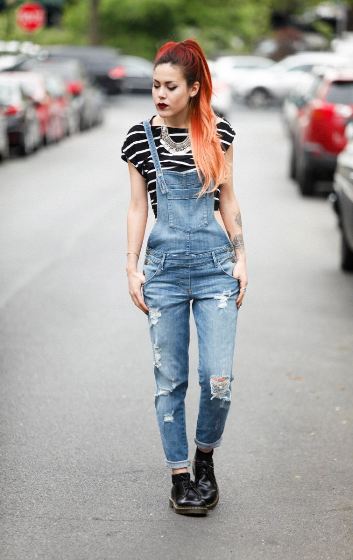 chunky silver necklace, worn with a striped, black and white t-shirt, and ripped 90s overalls, by young woman with dyed hair
