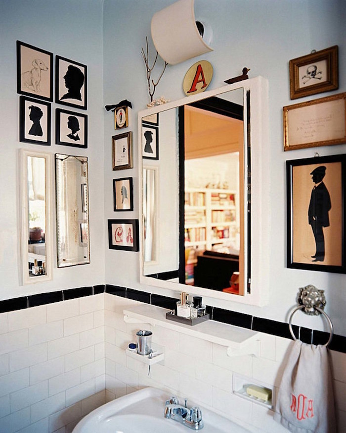 diy bathroom decor, lots of framed images, in different sizes, and one mirror, on the walls of a room, with a white ceramic sink