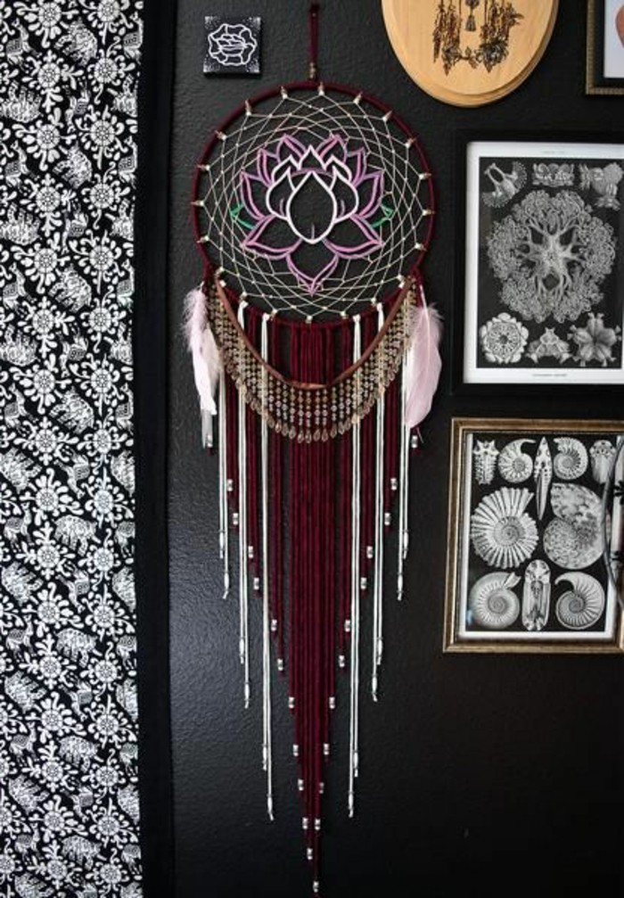 framed images and others, hung on a black wall, near a large dream catcher, with brown and white tassels, two pale pink feathers, and a lotus detail