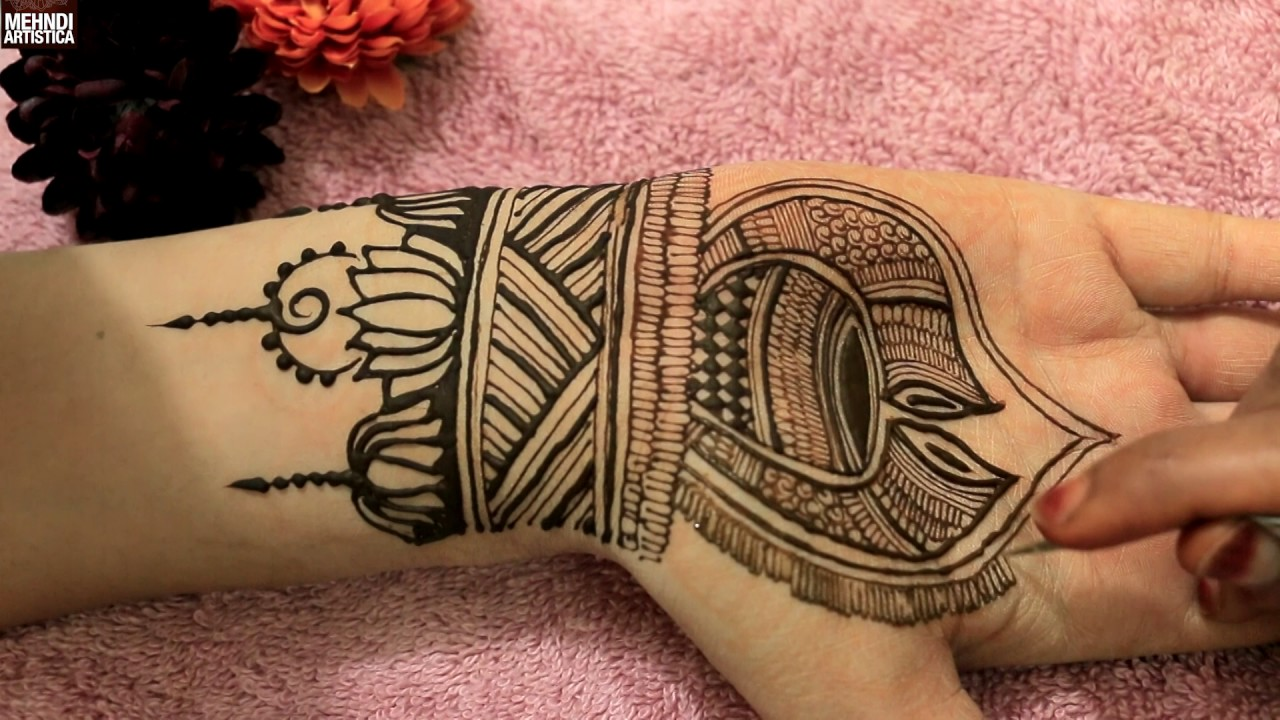 muslim henna hand tattoo designs, black lotus-like shapes, painted on a person's wrist and palm