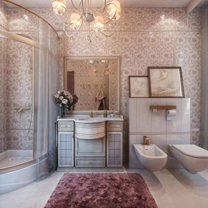 fluffy rug in purple, on the floor of a luxurious bathroom, with an antique style sink, a toilet bowl and a bidet, and a glass shower cabin