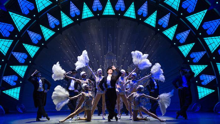female dancers holding ostrich fans, and male dancers, wearing smockings and top hats, posing on an elaborately decorated stage, bob crowley