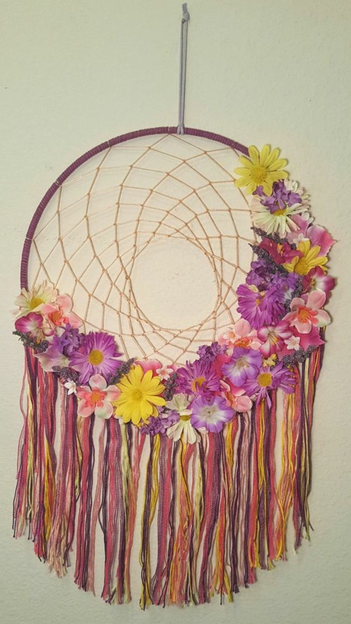 yellow and purple, cream and pink flowers, of different kinds, decorating a dream catcher, with many multicolored tassels, big dream catchers
