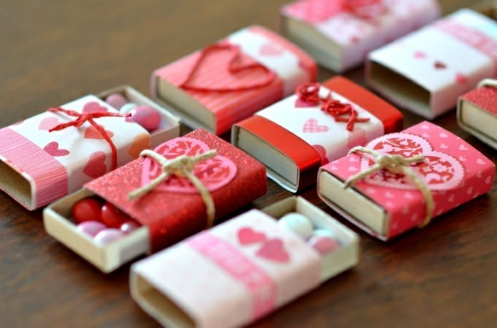 red and pink paper, with heart motifs, decorating several matchboxes, some opened to reveal white, pink adn red candies