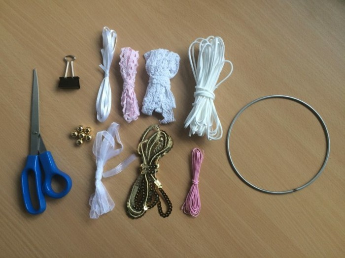 how to make a dreamcatcher, materials placed on a wooden surface, white leather rope, ribbons in different colors, gold chain and beads, scissors and a bulldog clip, a wire hoop