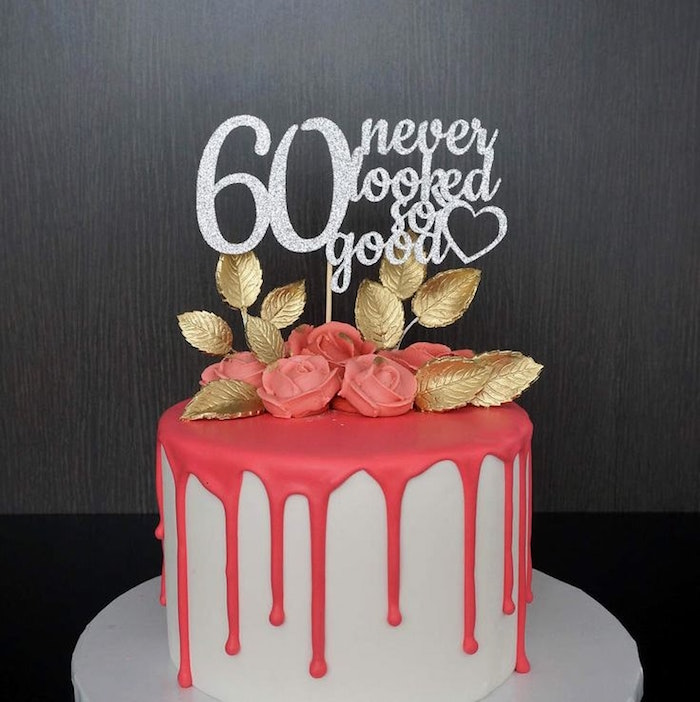 leaves made from gold fondant, and pink fondant roses, on a white cake, with a melting-effect pink frosting, and a sparkly silver topper, reading 60 never looked so good
