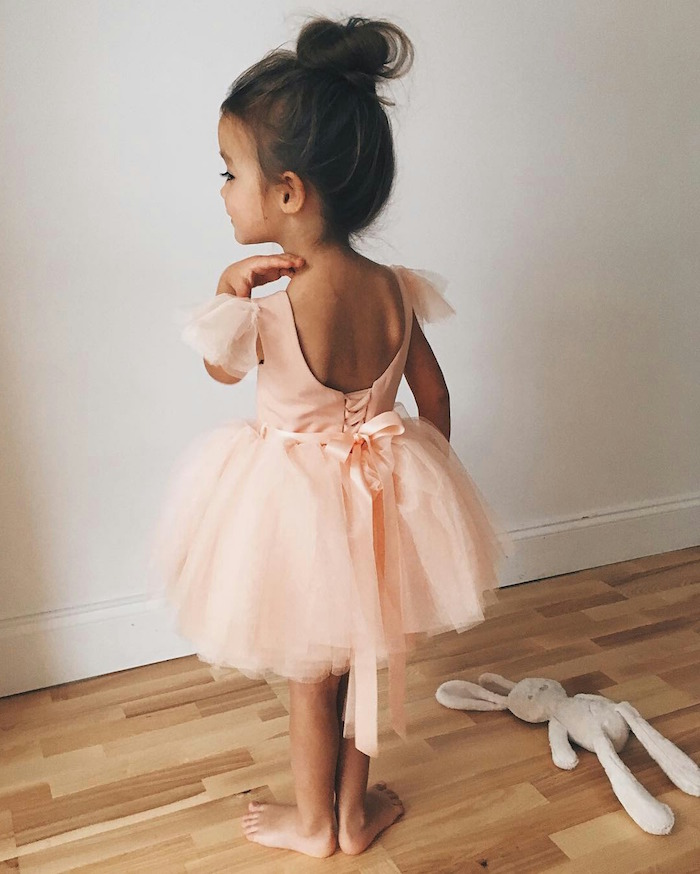little girl hairstyles, child in a pale peach ballerina outfit, with a tulle skirt, dark brunette hair, tied in a messy top knot