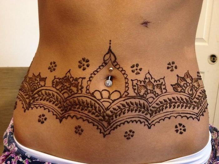 bare belly, decorated with brown henna patterns, featuring leaf and flower details, and a silver piercing