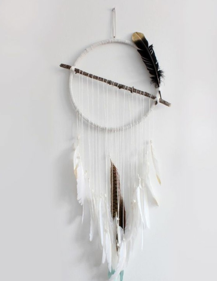 simple white diy dreamcatcher, with one brown branch, and several dark feathers, hanging on a white wall
